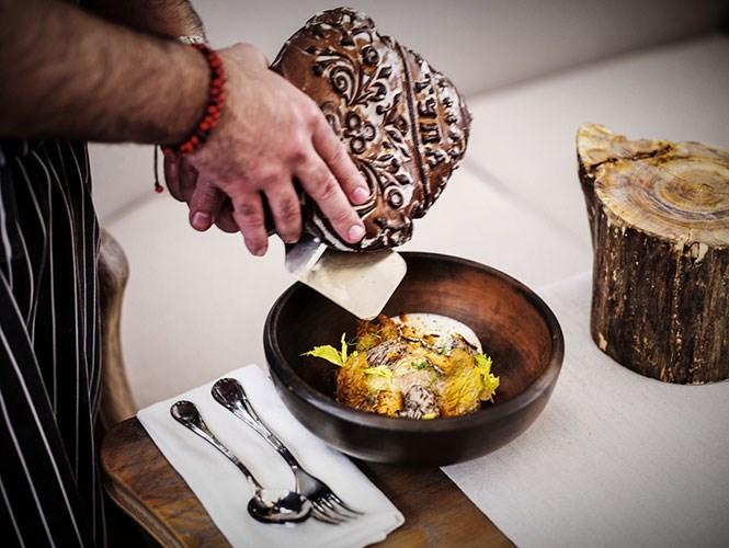 Владимир Мухин собственноручно натирает тульский пряник в ячневую кашу из нового меню «Белого кролика»; на запястье у него — браслет из мелкой фасоли, сувенир из Перу, страны, которой посвящен его новый ресторан «Чича».