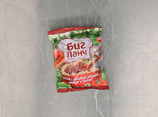 Лапша «Биг-ланч» с ароматной говядиной, грибами и зеленью — родом из города Донского Тульской области, где делается компанией, основанной вьетнамцами. Состав — едва ли не самый сложный из того, что мы попробовали. Например, ароматизатор «говядина» состоит из веществ вкусоароматических, глютамата, гуанилата, ацетата и инозината натрия, а также лимонной и уксусной кислоты (ароматизатор «грибы» чуть попроще). Но есть также молотый лавровый лист, зеленый лук, красный, черный и душистый перец, сушеные грибы, чеснок, говяжий жир, соевая паста, мускатный орех, гвоздика и тмин. Вот оно откуда — богатство вкуса. Возможны незначительные вкрапления сельдерея — но тут уж как кому повезет. Не рекомендуется (так и написано) употреблять в сухом виде. 10 рублей 33 копейки.