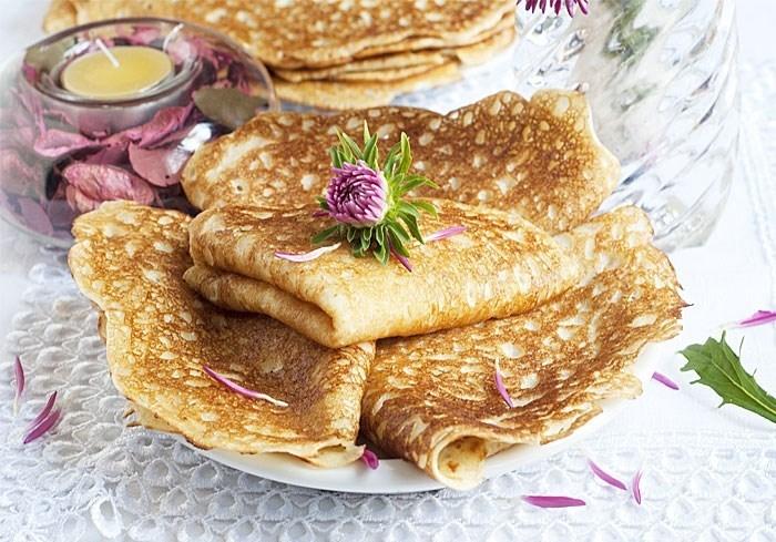 В миску со взбитыми с молоком яйцами добавить соль и, помешивая смесь деревянной ложечкой, постепенно добавить муку.